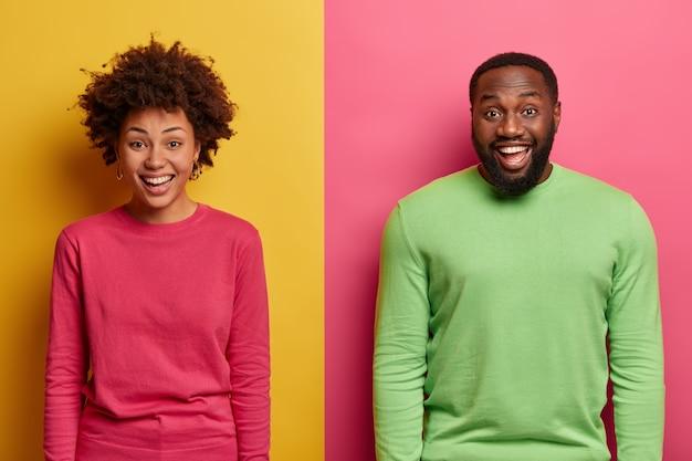 행복한 미소 아프리카 계 미국인 부부의 샷은 긍정적 인 감정을 표현하고, 분홍색과 녹색 점퍼를 착용하고, 즐거운 순간을 즐기고, 그들과 함께 일어난 재미있는 상황을 웃으며, 두 가지 색깔의 벽 위에 포즈를 취합니다.