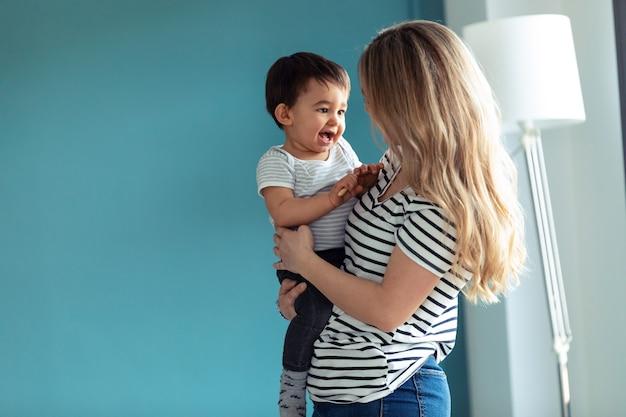 집에서 작은 아기와 함께 노는 행복한 웃는 젊은 어머니의 총.