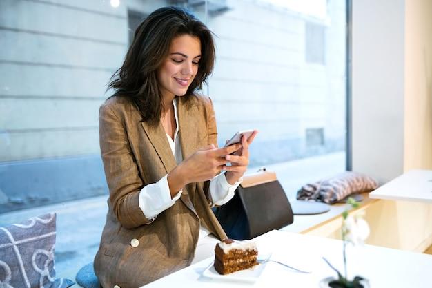커피숍에서 휴대전화로 문자 메시지를 보내는 행복한 젊은 여성 사업가의 총.