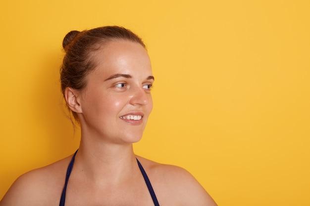 Снятый счастливой молодой кавказской женщины с нежной улыбкой, смотрит в сторону с очаровательным выражением, носит купальный костюм, имеет естественную красоту, изолированную над желтой стеной.
