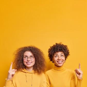 幸せな若い多様な女性のショットは、黄色の壁の上に隔離されたコピースペースの現在のアイテムまたは製品スタンドで上を指しています。人々のプロモーションと広告のコンセプト