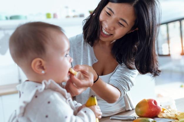 Выстрел счастливой молодой матери, кормящей ее милую девочку с бананом на кухне дома.