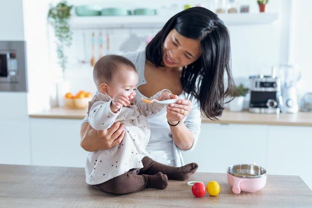 Выстрел счастливой молодой матери, кормящей ее милую девочку фруктовой кашей на кухне дома.