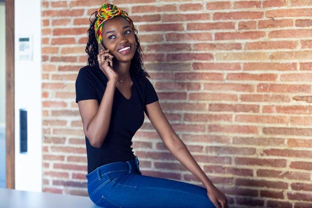 벽 앞의 테이블에 앉아 있는 동안 휴대전화로 통화하는 행복한 젊은 여성의 샷.