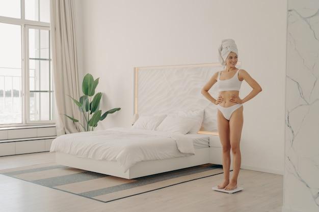 Выстрел здоровой стройной молодой женщины в белом нижнем белье с головой, завернутой в банное полотенце, стоящей на весах в спальне, счастливой видеть свою потерю веса. концепция здорового образа жизни и ухода за телом
