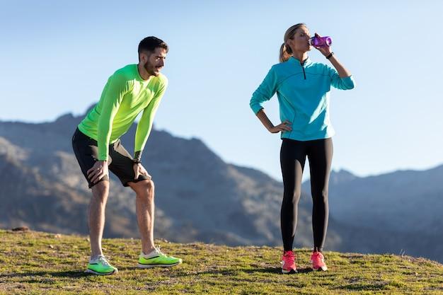 여자가 산에서 물을 마시는 동안 실행 후 휴식을 취하는 건강한 젊은 부부의 샷.