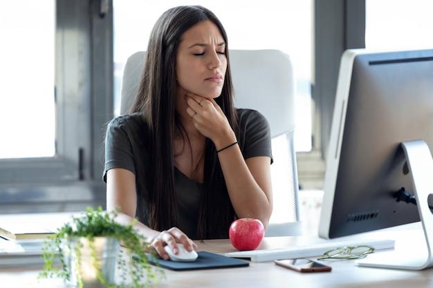 オフィスでコンピューターを使用して作業しているひどい喉の痛みを持つ病気の若いビジネス女性のショット。