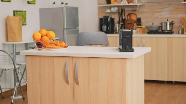 誰もいないキッチンのショット。テクノロジーと家具、装飾と建築、快適な部屋を備えた居心地の良いインテリアのコーヒーマシン付きのモダンなダイニングルーム