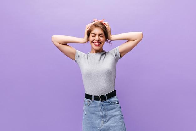 紫色の背景にデニムスカートの女性のショット。灰色のトレンディなシャツを着たうれしそうな魅力的な女性は、孤立した背景にファンがいます。