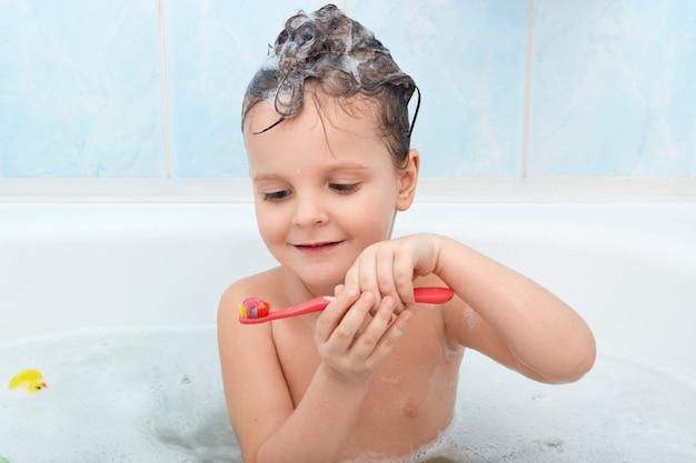 Выстрел из маленького ребенка, чистящего зубы, принимая ванну, очаровательная мокрая леди держит красную зубную щетку