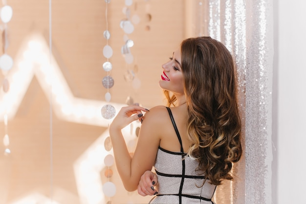 明るい星と輝く壁でパーティーを楽しんでいる長髪の女性のショット。輝くドレスを着た女性は目を閉じて優しく微笑んだ。