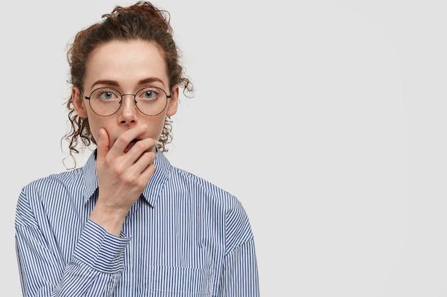 素敵な気配りのある真面目なヨーロッパの女性のショットは、口に手を保ち、大きな関心を持って必要な情報を聞き、丸い眼鏡をかけ、空白のある白い壁にポーズをとる