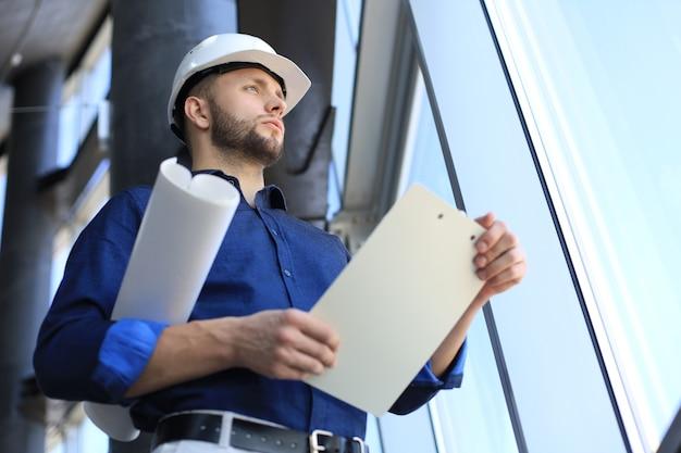 ヘルメットをかぶって新しい建物を調べている男性建築家のショット。