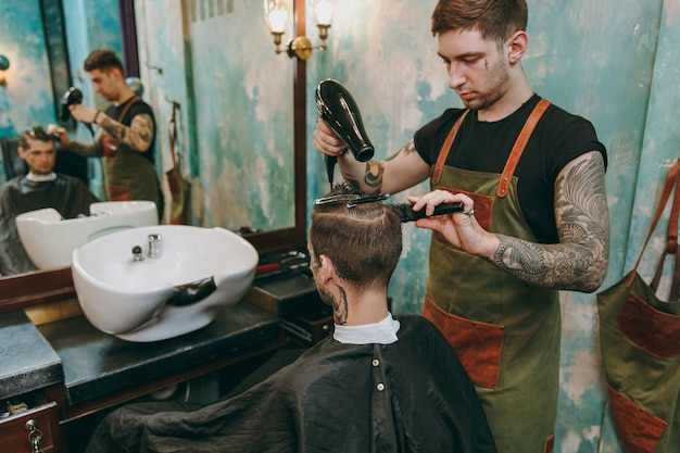 이발소에서 트렌디한 이발을 하는 남자의 샷. 문신을 한 남성 헤어스타일리스트는 고객에게 서비스를 제공하고 헤어드라이어로 머리를 말립니다. 무료 사진