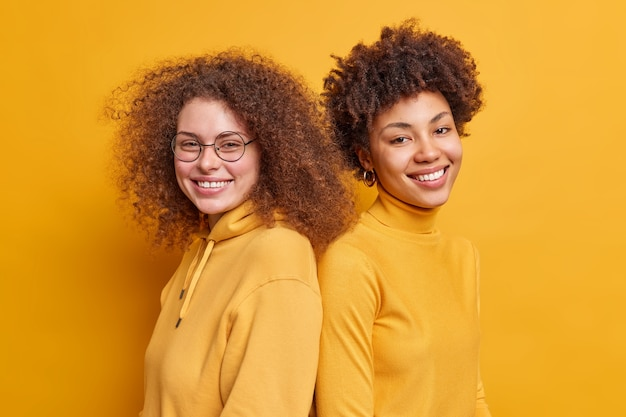 혼혈 여성의 샷은 행복한 표정으로 서로 다시 서서 노란색 벽 위에 고립 된 만족스러운 착용 캐주얼 옷을 느낍니다. 사람들의 감정 관계 개념.