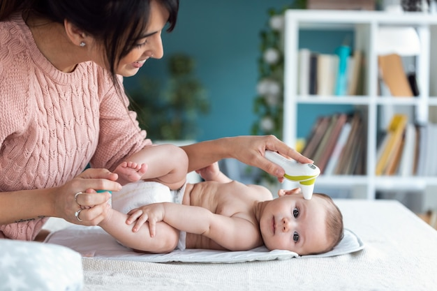 집에서 적외선 온도계로 아기의 온도를 측정하는 어머니의 사진.