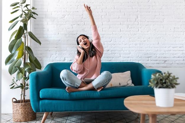 집에서 소파에 앉아 디지털 태블릿으로 음악을 듣고 있는 동기 부여된 젊은 여성의 샷.