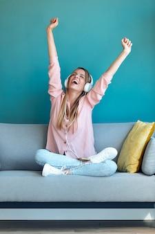 집에서 소파에 앉아 스마트폰으로 음악을 듣는 동기부여된 젊은 여성의 사진.