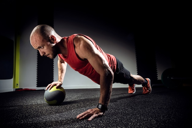 暗いスタジオで薬のボールで腕立て伏せをしている筋肉の若い男のショット。
