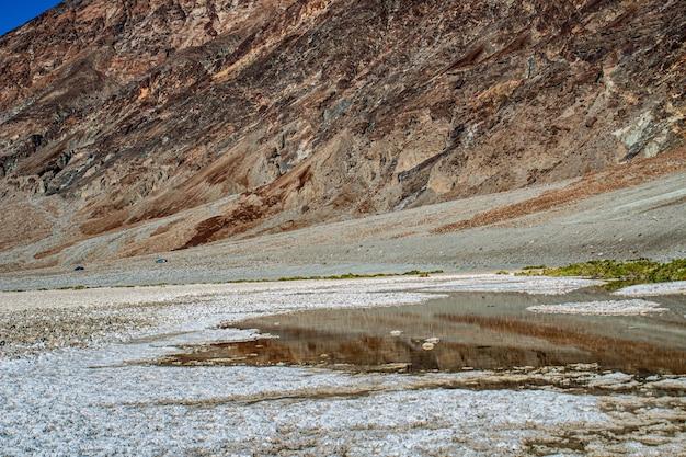 岩だらけの丘の前の部分的に乾燥した水たまりのショット