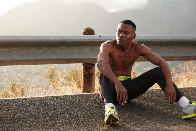 エネルギーに満ちた物思いにふける黒人男性のショットは、屋外のアスファルトに座って、ランニングやスポーツ競技の準備を終え、トレーナーを濡らし、健康的なライフスタイルを導き、視線を脇に置きます。有酸素運動。