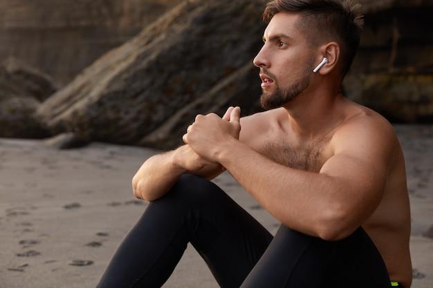 잠겨있는 백인 남성 선수의 총은 함께 손을 유지하고, 모래 해변에 앉아, 레깅스를 착용