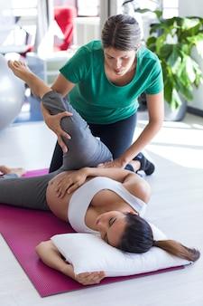 Выстрел физиотерапевта, помогающего красивой беременной женщине делать упражнения пилатеса, готовящиеся к родам.