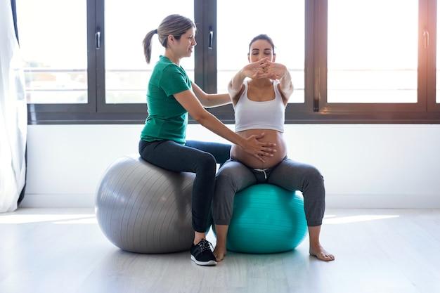 理学療法士が出産の準備をするボールでピラティスエクササイズをするために美しい妊婦を助けるショット。
