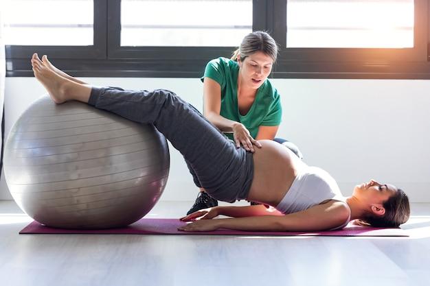 Выстрел физиотерапевта, помогающего красивой беременной женщине делать упражнения пилатеса с мячом, готовясь к родам.