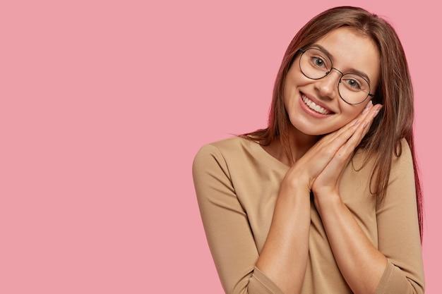 満足している若い女性のショットは、昼寝をしているように手のひらをまとめ、ポジティブな表情を持ち、健康で清潔な肌、黒髪、右側にコピースペースがあるピンクの壁に立っています