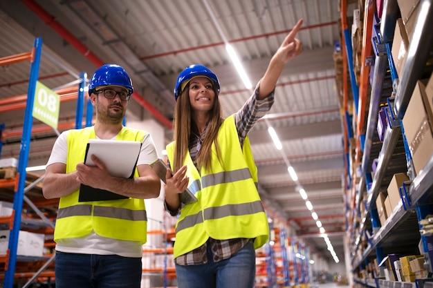 Снимок позитивных жизнерадостных складских рабочих, вместе проверяющих инвентарь на полках и контролирующих распределение продуктов на большом складе