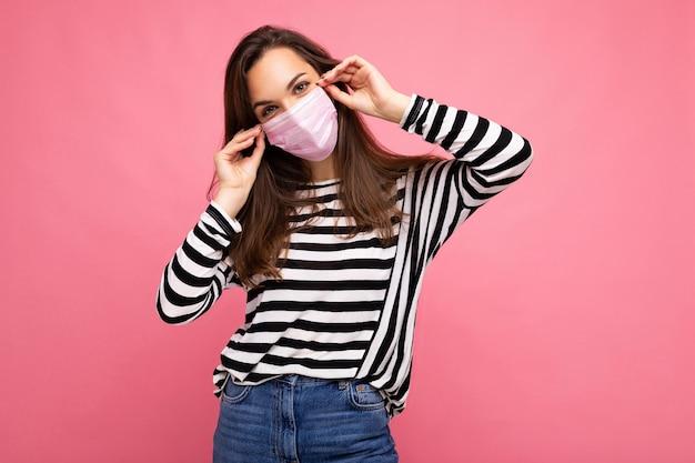 分離された内側のフェイスマスクを身に着けているポジティブな若い魅力的な女性のショット