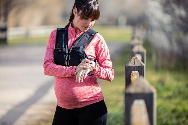 Снимок беременной молодой женщины, использующей свои умные часы во время подготовки к бегу в парке.