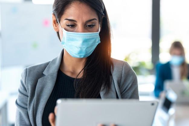 Снимок красивой деловой женщины в гигиенической маске во время работы со своим цифровым планшетом в коворкинге.