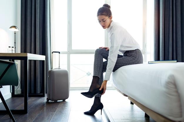 그녀의 호텔 방에서 일 후 하이힐 신발을 벗고 예쁜 사업가의 총.