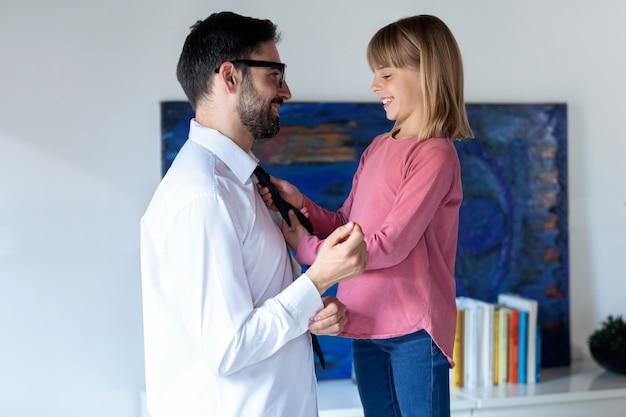 집에서 일하러 가기 전에 아빠의 넥타이를 매는 예쁜 소녀의 사진.