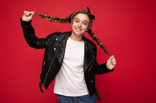 スタイリッシュな黒を身に着けているおさげ髪のかなりポジティブな笑顔のブルネットの小さな女性のティーンエイジャーのショット