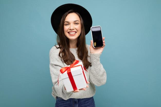 예쁜 미소 긍정적 인 젊은 brunet 여자의 총 검은 입고 파란색 배경 벽에 고립