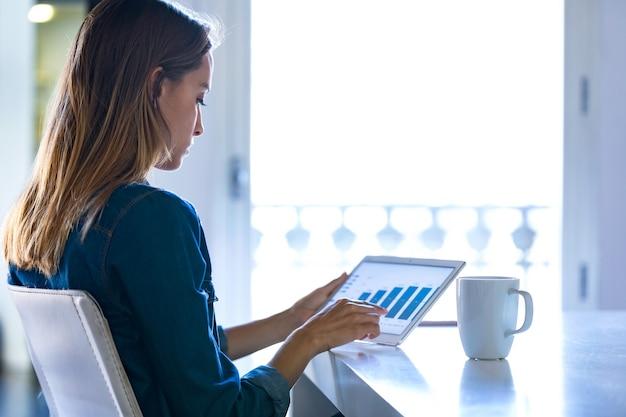 オフィスでデジタルタブレットを使用して作業しているかなり若いビジネスウーマンのショット。