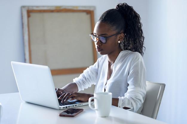 オフィスでラップトップを使用して作業しているかなり若いビジネスウーマンのショット。