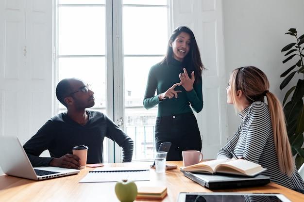 コワーキングプレイスで同僚にプロジェクトを説明しているかなり若い起業家の女性のショット。