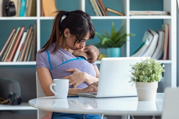 Снимок довольно молодой матери, целующей своего ребенка в слинге во время работы с ноутбуком дома.