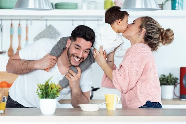 집에서 부엌에서 아버지와 즐거운 시간을 보내면서 아기 아들에게 키스하는 예쁜 젊은 어머니의 샷.