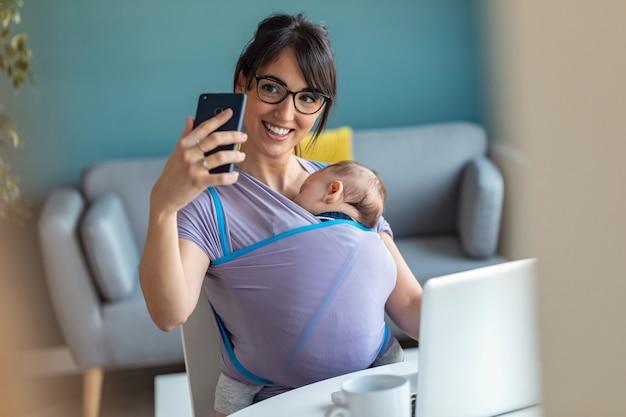 Снимок довольно молодой матери с ребенком в слинге, делающей селфи во время работы с ноутбуком дома.
