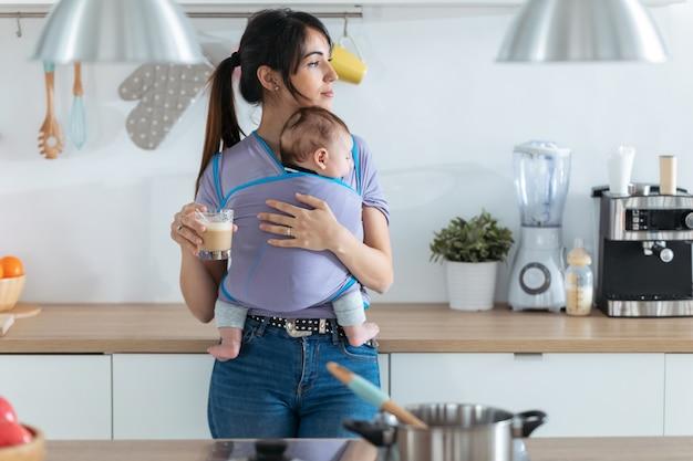 집에서 부엌에서 커피를 마시는 슬링에 작은 아기와 함께 예쁜 젊은 어머니의 총.