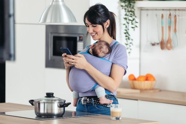 집에 있는 부엌에서 휴대전화를 사용하여 슬링에 작은 아기를 안고 있는 예쁜 젊은 어머니의 사진.