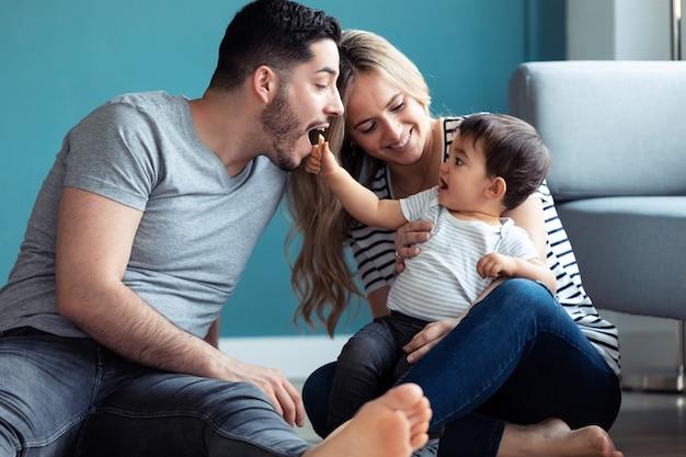 집에서 바닥에 앉아 있는 동안 아기 아들과 노는 예쁜 젊은 부모의 총.