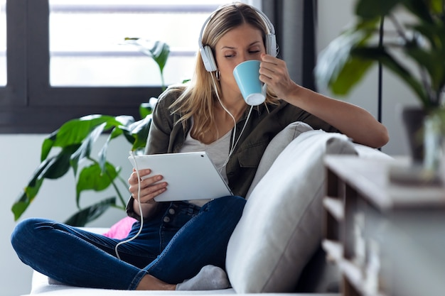 집에 있는 소파에서 디지털 태블릿으로 음악을 들으며 커피 한 잔을 마시는 예쁜 젊은 여성의 사진.