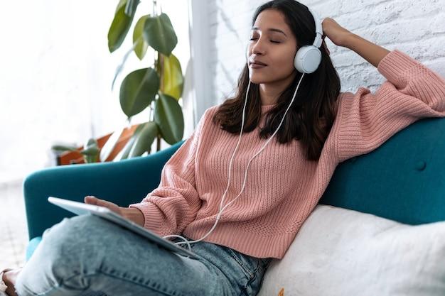 디지털 태블릿으로 음악을 듣고 집에서 소파에 앉아 휴식을 취하는 예쁜 젊은 여성의 사진.