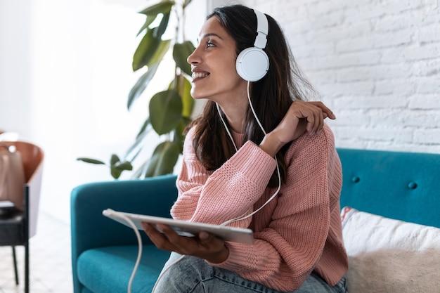 집에서 소파에 앉아 디지털 태블릿으로 음악을 듣는 예쁜 젊은 여성의 사진.